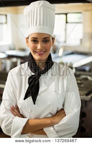 Portrait of chef head standing with arms crossed in commercial kitchen