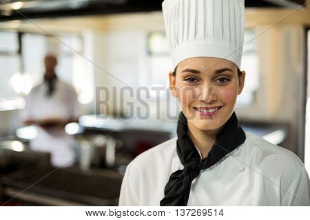 Portrait of smiling chef head standing in commercial kitchen