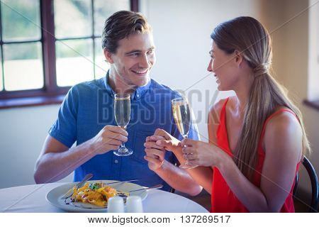Happy young couple toasting champagne flutes while having lunch in a restaurant