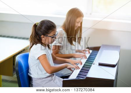 Two girls playing the piano at the music school selective focus