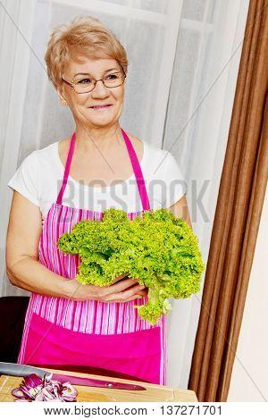 Senior woman tearing green lettuce