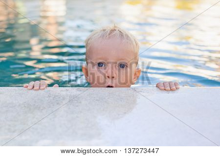 Children swimming lesson - funny face portrait of little baby boy in swimming pool. Active healthy lifestyle water sport physical activity and fun with parents on summer family holiday with child.