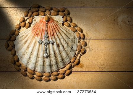 Scallop seashell and wooden rosary beads with a silver crucifix on a wooden background. Symbols of Christian pilgrimage