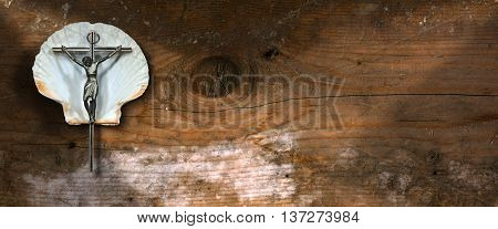 Silver crucifix (Jesus Christ on the cross) on a white scallop seashell on a wooden background. Symbol of Christian pilgrimage
