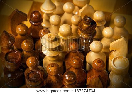 Detail of wooden chess pieces on the wooden chess board with dark shadows
