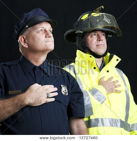 Policeman and fireman saying the pledge of allegiance.  Photographed on black background.