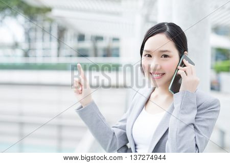 business woman pointing show and smile speak smart phone in office asian beauty