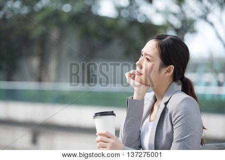thinking business woman hold coffee cup with office background asian shot in Hong Kong