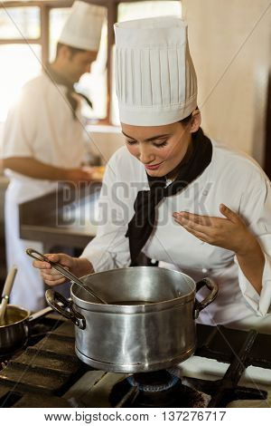Smiling head chef stirring in cooking pot in a commercial kitchen