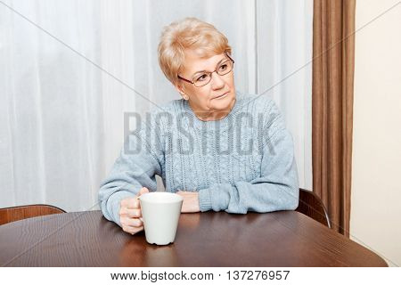 Senior woman sitting at the desk and drinking coffee or tea