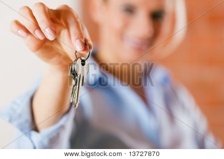 Realtor is giving the keys to an apartment to some clients �¢�?�? focus on the keys