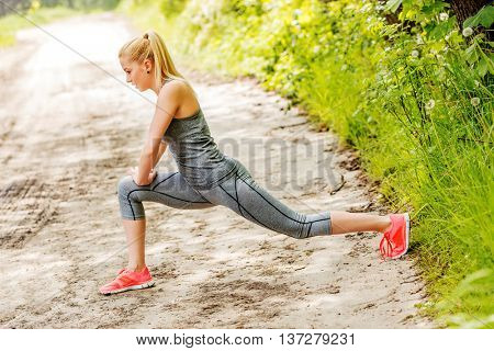Young sportswoman stretching and preparing to run.