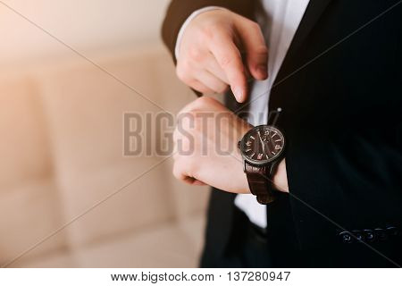 businessman in black costume look at his swiss wristwatch on his hand and watching the time