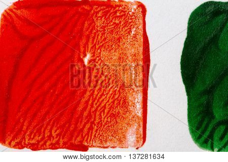 Closeup view of abstract hand painted red and green acrylic art background on paper texture. Fragment of artwork
