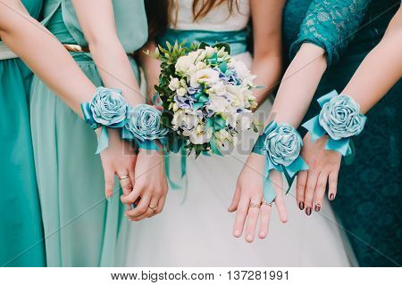 the bride with a yellow bouquet of roses and bridesmaids in blue and yellow dresses