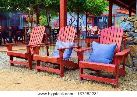 Rustic wooden chairs taken in a modern courtyard garden