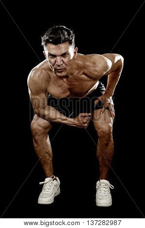 strong and fit man with ripped body muscles doing squat exercises showing defined shoulders and biceps in naked torso isolated on black background in sport condition and training concept