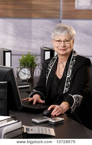 Portrait of senior businesswoman sitting in office, using desktop computer, looking at camera, smiling.?