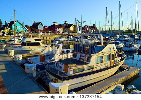 June 27, 2016 in Long Beach, CA:  Sail Boats, yachts, and motor boats at Long Beach Harbor where locals and tourists can travel on rental boats or their own boats with the colorful buildings of Shoreline Village beyond which consist of retail stores and r