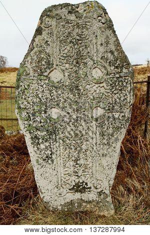 Old stone celtic cross in Scottish highlands