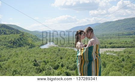 Young seductive naked couple covered by blanket softly embrasing on the green mountains background. Harmony with nature.