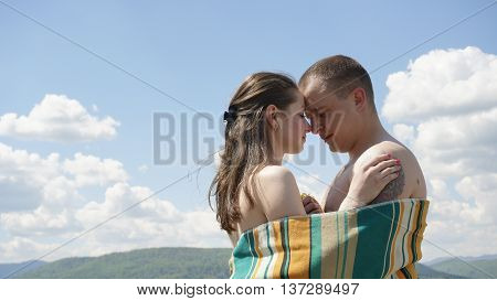 Young beautiful naked couple covered by blanket softly embrasing on the green mountains background. Concept of true happiness.