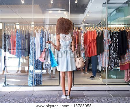 Rearview of a young woman carrying shopping bags and looking through the window of a clothing store while shopping at the mall