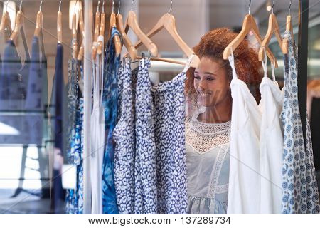 Attractive young woman with curly hair browsing through clothes hanging on racks while standing in a clothing store