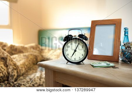 Black Retro Alarm Clock And Bed In Morning Light, 7.00 Am Alarm Clock In Morning. Shallow Depth Of F
