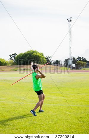 Rear view of an athlete about to throw a javelin in the stadium