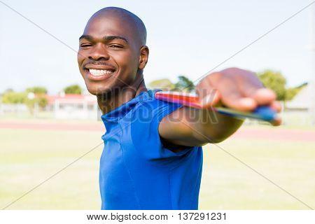 Portrait of athlete standing with javelin in stadium