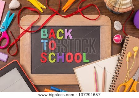 Back To School letters on small blackboard with school supplies on wooden table