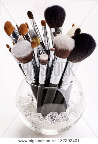 Makeup brushes in a glass vase with crystals on white background