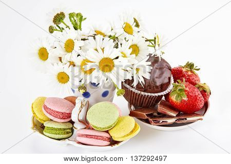 Camomiles in vase macaroons on saucer with strawberry and chocolate