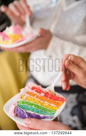 People eating delicious rainbow cake. Homemade colorful cake for birthday party. Hands with piece of cake. Close-up of hands holding spoons about to slice into a rainbow cakes.