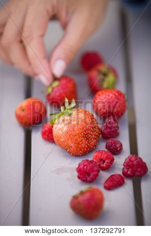 Woman's hand taking fresh organic strawberries and raspberries. Berries on the grey background. Garden harvest on the table. Snack time. Natural and healthy dessert. Fingers picking a berry.
