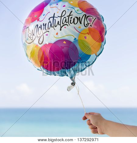 Woman's hand holding colorful baloon on the blue sky background. Congratulation baloon in the air. Ocean background. Sunny day in Miami. Celebration. Birthday. Present