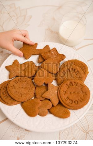 A hand of a child taking freshly made home holiday cookies in shapes of starts hearts and circuses. Plate of Christmas treats. Dessert for a family.