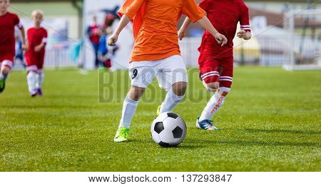 Young boys playing football soccer game on sports field. Running soccer players in sport shirts. Kids running and kicking soccer ball.