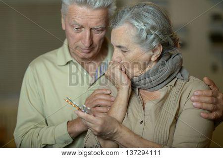 Portrait of ill senior couple with pills