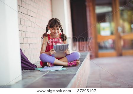 Girl looking at her digital tablet with legs crossed