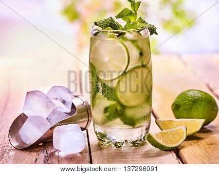 Alcohol drink. On wooden boards is glass with alcohol drink and ice cubes. A drink number thirty four cocktail mohito and scoop ice . Country life cocktail . Outdoor. Light background.