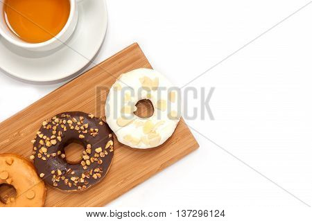 Delicious Donuts With Icing And Tae In Wood Plate Isolated On White