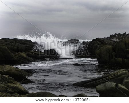 A view of waves breaking into a gulley between rocks.