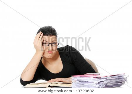 Bored young student woman at the desk , isolated on white background