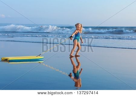 Little baby girl - young surfer with bodyboard has fun on sea beach. Family lifestyle people outdoor water sport lessons and swimming activity on summer vacation with child in adventure surf camp.