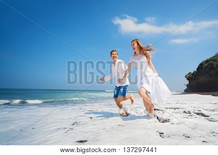 Happy newlywed family on honeymoon holiday - just married loving couple run with fun by black sand beach along sea surf. Active lifestyle people outdoor activity on summer vacation on tropical island.
