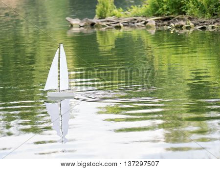 Radio controlled boat sailing on water - lake or pond in summer park
