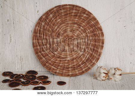 Wicker brown place mat with cotton flowers.