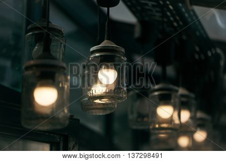 Original ceiling lamps of glass jars and bulbs lighting interior decor on grey blurred background